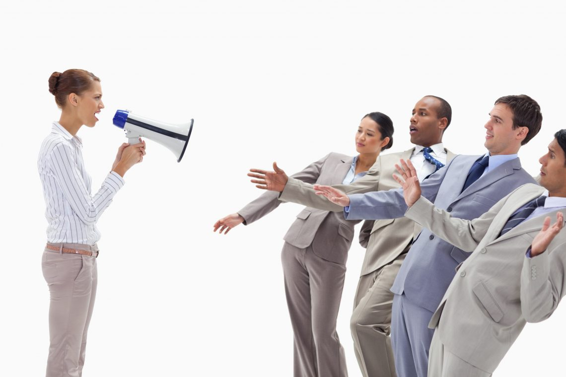 Woman yelling at people dressed in suits through a megaphone